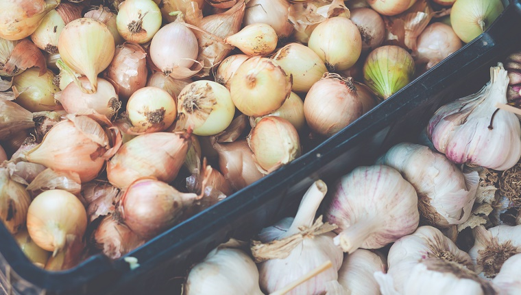 Full frame, overhead view, of onions and garlic on farmer's market.