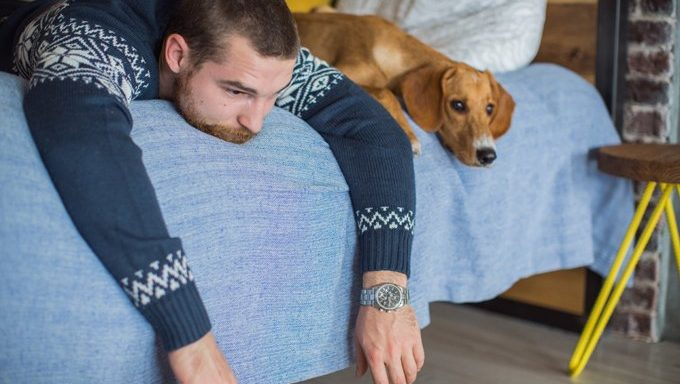 man lying with dog on bed
