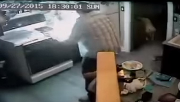 Security camera footage shows a man grabbing a burning pizza box off of the kitchen stove. A dog watches from the hallway.