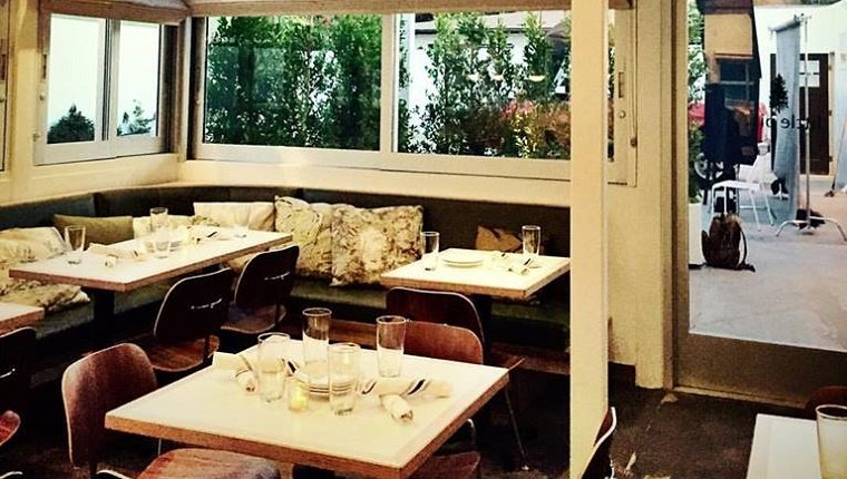 Tables at the Little Pine restaurant are set. The booths have throw pillows and there is a view of a patio garden out the window.