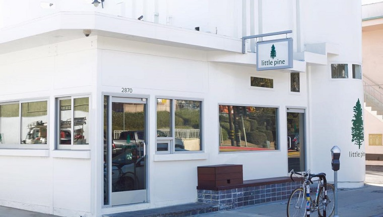 The Little Pine restaurant is a small white building with lots of windows.