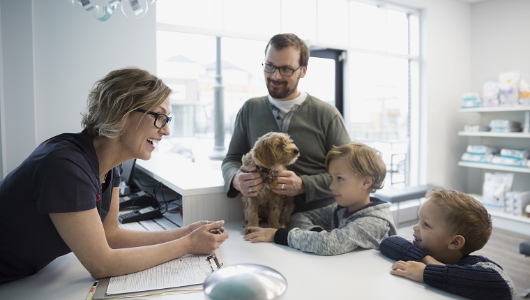 Veterinarian greeting family with dog at reception