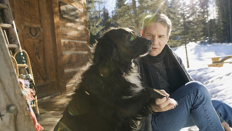 Man shaking dogs paw outside log cabin