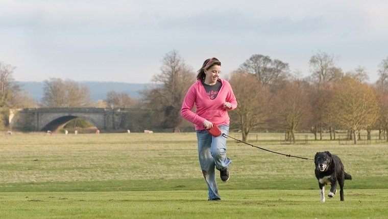 teenager with her dog running thriugh a country park