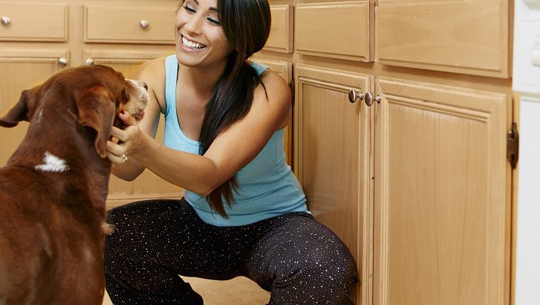 Woman playing with dog in kitchen