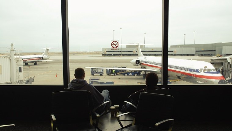 Silhouette of people watching thru an airport window. Parked planes and airport.