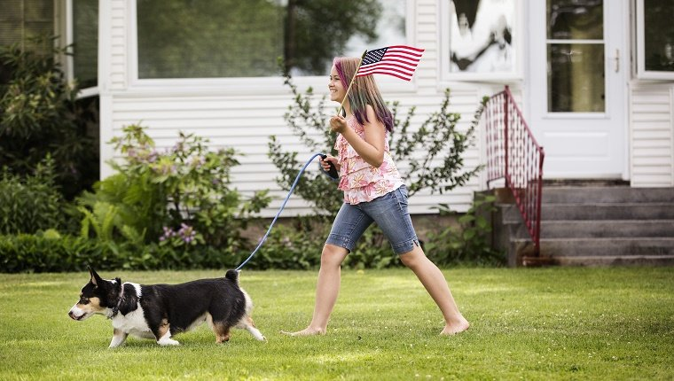 Mixed race girl walking dog with American flag