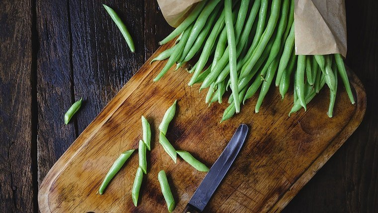 Directly Above Shot Of Green Beans And Knife On Cutting Board
