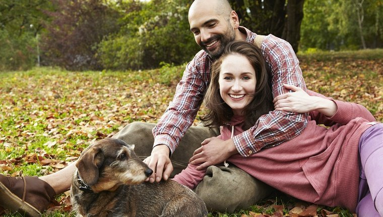 young couple sitting in a park on the lawn with their dog.