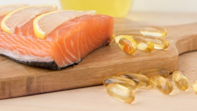 Fish oil, cod liver oil capsules and salmon fillet on wooden surface