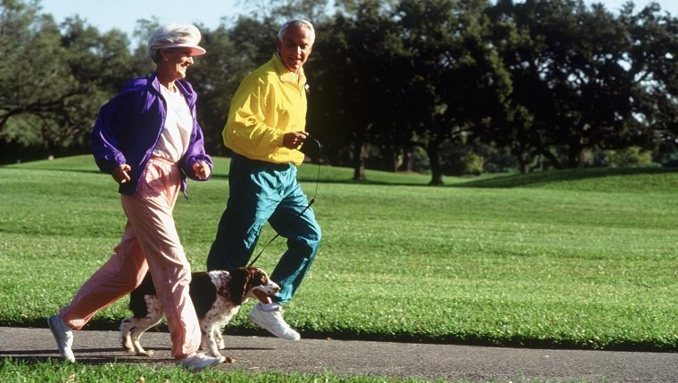 Senior couple jogging in park with their dog
