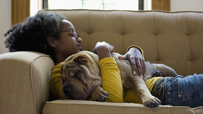 young girl cuddling shar pei on couch
