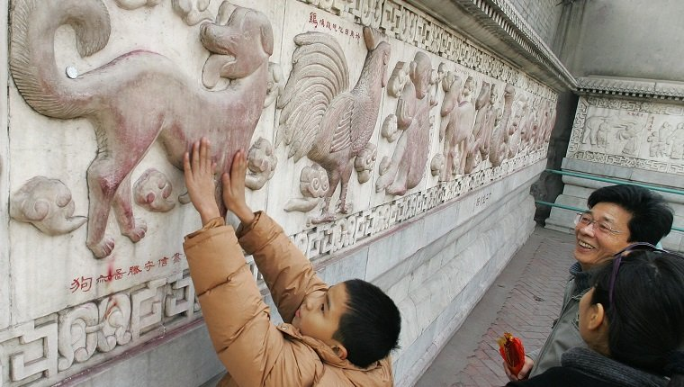 BEIJING, CHINA: A child rubs his hands for good luck on a bas-relief sculpture of a dog along a wall depicting the twelve animals of the lunar calendar, 27 January 2006, at the White Cloud Taoist Temple (Baiyun Guan) in Beijing. Founded in A.D 739, the White Cloud Temple is one of the oldest Taoist temples in northern China and attracts thousands of visitors for its temple fair during the Spring Festival holidays to celebrate the Lunar New Year, which falls on 29 January with the Year of the Dog. AFP PHOTO/Frederic J. BROWN (Photo credit should read FREDERIC J. BROWN/AFP/Getty Images)