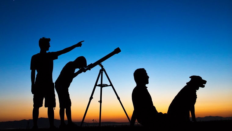 Dad and sons on a clear night looking thru a telescope