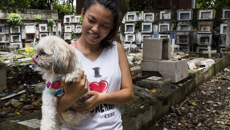 Young woman with her dog, at Calamba Cemetery, Cebu City, Cebu, Philippines