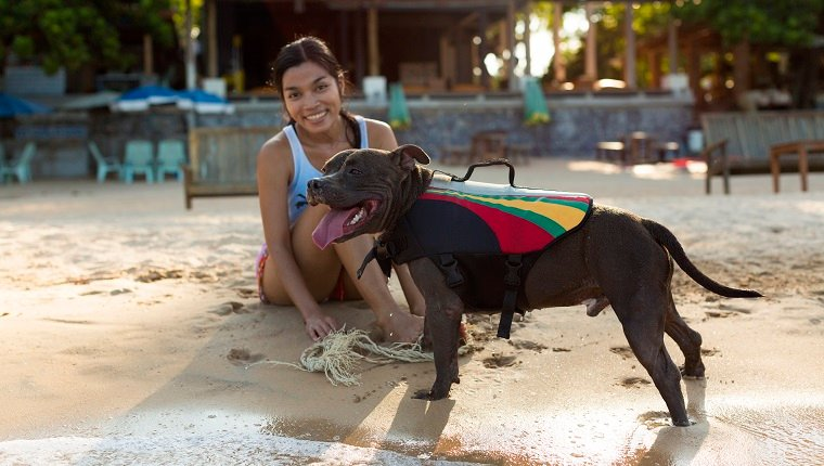 A young woman is enjoying the company of her dog on a tropical beach.