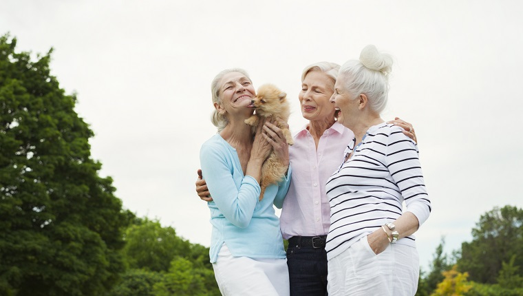 Senior women holding dog in park