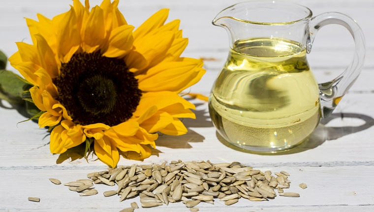 sunflower seeds with sunflower oil in small glass jar and sunflower blossom on white table