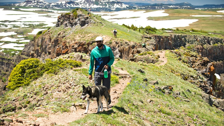 A man and his dog hiking near The Devils Causeway in Yampa, Colorado.