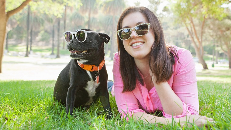 Portrait of young woman and dog lying in park wearing sunglasses