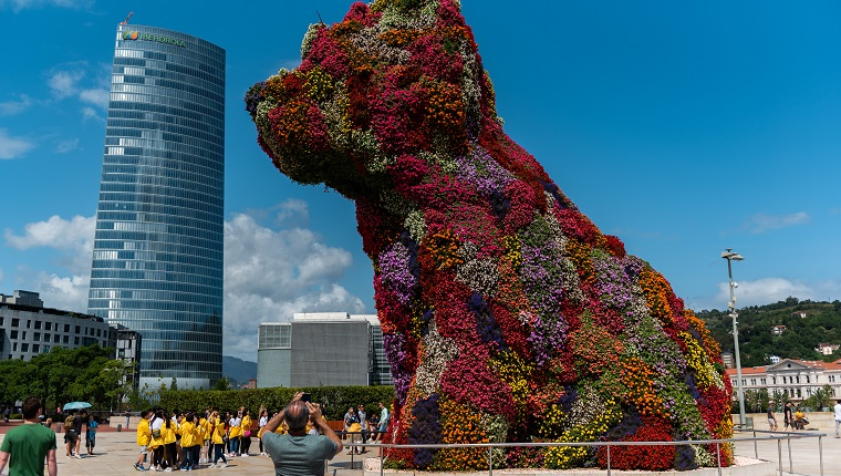BILBAO, VIZCAYA, SPAIN - 2019/07/30: Jeff Koons Puppy dog sculpture in Guggenheim museum next to Iberdrola tower.
