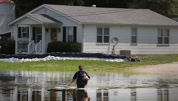 BARNHART, MISSOURI - MAY 31: David Nibarger walks through floodwater from the the Mississippi River as he leaves his home with his dog Tiny under his arm on May 31, 2019 in Barnhart, Missouri. The middle-section of the country has been experiencing major flooding since mid-March especially along the Missouri, Arkansas, and Mississippi Rivers. Towns along the Mississippi River have been experiencing the longest stretch of major flooding from the river in nearly a century.