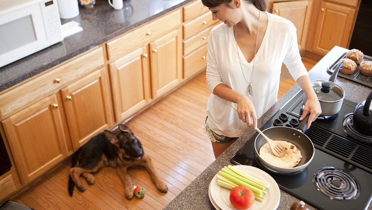 Woman cooking in the kitchen and her puppy sitting next to her