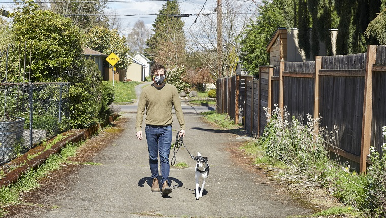 Portrait of a man walking his dog down an alley in spring, wearing a home made face mask.